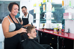 Little boy getting hair cut by woman hairdresser Stock Photo