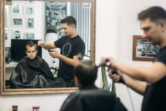 Little boy getting haircut by barber while sitting in chair at barbershop Royalty Free Stock Photography