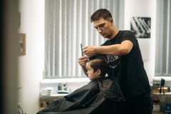 Little boy getting haircut by barber while sitting in chair at barbershop Stock Photos