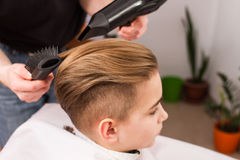Little boy getting haircut by barber Stock Image