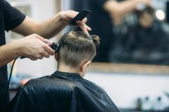 Little Boy Getting Haircut By Barber While Sitting In Chair At Barbershop. Royalty Free Stock Photography