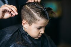Little Boy Getting Haircut By Barber While Sitting In Chair At Barbershop. Royalty Free Stock Photo