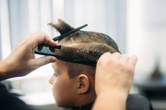 Little Boy Getting Haircut By Barber While Sitting In Chair At Barbershop. Royalty Free Stock Image