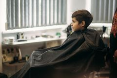 Little boy getting haircut by barber while sitting in chair at barbershop Royalty Free Stock Photos