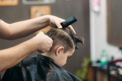 Little boy getting haircut by barber while sitting in chair at barbershop Stock Images