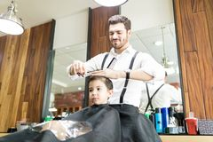 Little Boy Is Getting Haircut By Hairdresser At Barber Shop stock photography
