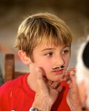 Boy Face Painting. Little boy getting a mustache painted on his face Stock Photos