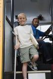Little Boy Getting Off School Bus. Portrait of a cute little boy getting down from school bus Stock Photography