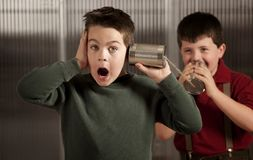 Little boy getting shocking message on tin can pho Royalty Free Stock Photography