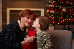Little boy getting surprise at christmas. Little boy leaning to smiling grandmother with eyes closed, getting surprise christmas present Royalty Free Stock Photography