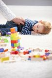 Little boy getting tired in playing. Sweet little boy getting tired in playing, laying on floor, among cubes Royalty Free Stock Image