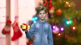 Little boy with gift box on blur Christmas background. Handsome kid holding gift box with one hand. Christmas background with shining lights stock footage