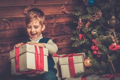 Little boy with gift box in wooden house interior Stock Images