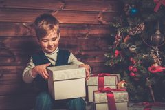 Little boy with gift box in wooden house interior Royalty Free Stock Photography