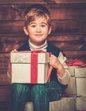 Little boy with gift box in wooden house interior Stock Photo