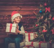 Little boy with gift box in wooden house interior Stock Photography