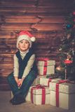 Little boy with gift box in wooden house interior Stock Photos