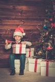Little boy with gift box in wooden house interior Royalty Free Stock Image