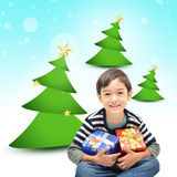 Little boy  with gift and Christmas tree background Stock Photo