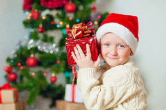 Little boy  with gifts near a Christmas tree Royalty Free Stock Photos