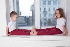 The little boy and girl alone at home watching in the window. The little boy and girl alone at home watching window stock photos