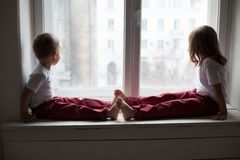 The little boy and girl alone at home watching in the window. The little boy and girl alone at home watching window stock images