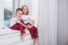 The little boy and girl alone at home watching in the window royalty free stock photography