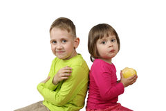 Little boy and girl with apple in hands sitting back to back. Isolated on white background Stock Images