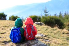 Little boy and girl with backpacks having rest in Royalty Free Stock Photo