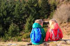 Little boy and girl with backpacks having rest in mountains Stock Photo