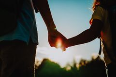 Little boy and girl with backpacks holding hands at sunset. Go to school Stock Image