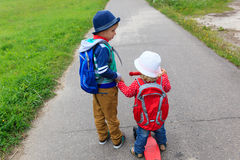 Little boy and girl with backpacks on the street, kids go to school Stock Images