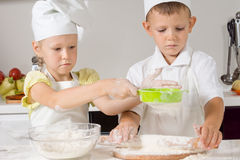 Little boy and girl baking in the kitchen. Little boy and girl in white toques and aprons baking in the kitchen making dough and working as a team as the girl royalty free stock photos
