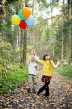 Little boy and girl with balloons in a forest Stock Photo