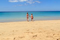 The boy and the girl on the beach go to sea together, Fuerteventura- Canary Islands Stock Photography