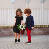 Little boy and girl with big lilac bouquet Stock Images
