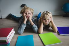Little boy and girl bored tired stressed of doing homework. Exhausted kids stock photos