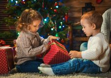 Little boy and girl brother and sister at home with a Christmas. Tree, presents and candles celebrating christmas Royalty Free Stock Image