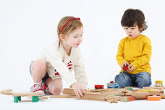 Little boy and girl build railway from wooden parts stock image