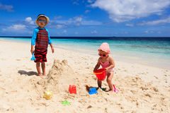Little boy and girl building sandcastle on beach Stock Photo