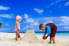 Little boy and girl building sandcastle on summer Stock Images