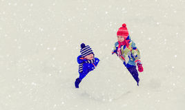 Little boy and girl building snowman in winter. Kids winter activities Stock Image