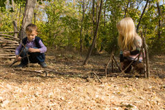 Little boy and girl building wooden tepees Royalty Free Stock Photos