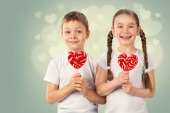 Little boy and girl with candy red lollipop in heart shape. Valentine`s day art portrait. Stock Photos