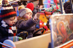 Little boy and girl on a carousel at Christmas market Royalty Free Stock Photos