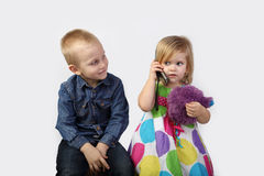Little boy and girl with cell phone on gray Stock Photo