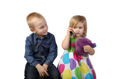 Little boy and girl with cell phone on white Royalty Free Stock Photos