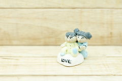 Little boy and girl ceramic dolls on wood pattern background Royalty Free Stock Image