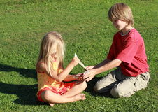 Little boy and girl changing money. Little boy and barefoot girl changing euros and dollars royalty free stock photo