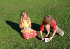 Little boy and girl counting money. Little boy and barefoot girl holding lots of money royalty free stock images